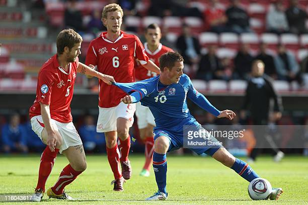Gylfi Sigurdsson of Iceland has his shirt pulled by Jonathan Rossini of Switzerland during the UEFA European Under21 Championship Group A match...