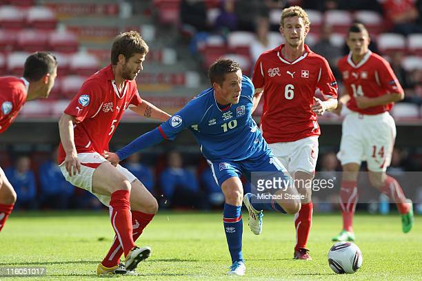 Gylfi Sigurdsson of Iceland is held up by Jonathan Rossini of Switzerland during the UEFA European Under21 Championship Group A match between...