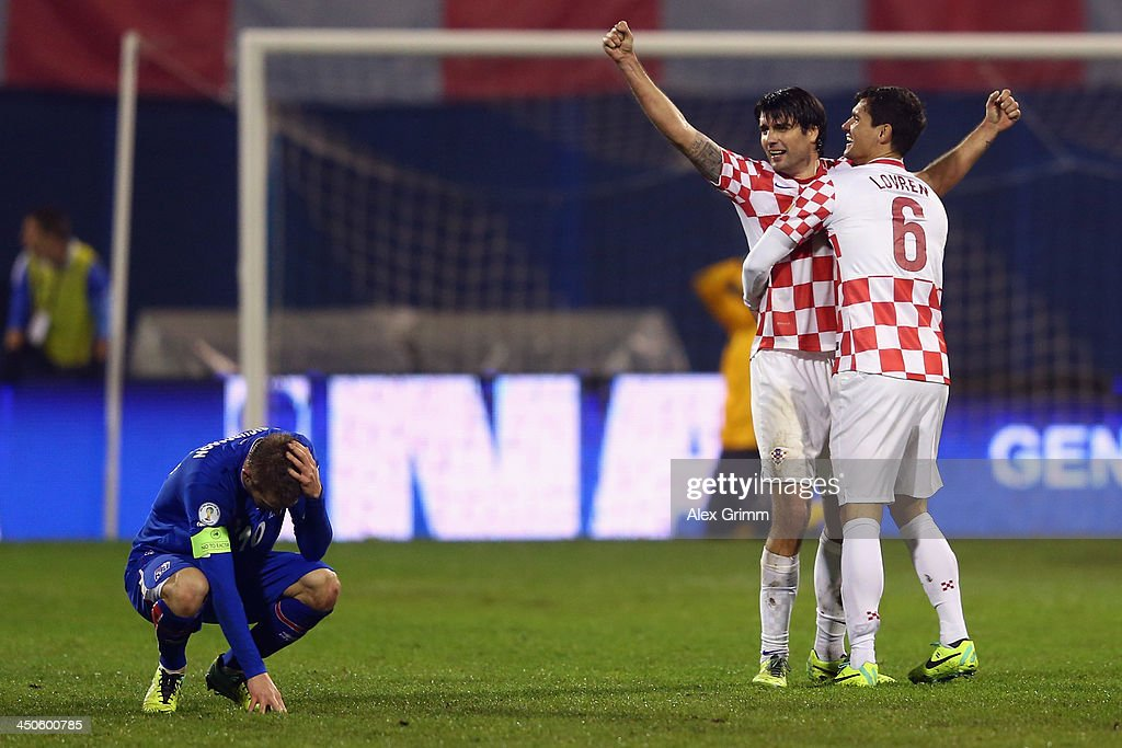 Gylfi Sigurdsson (L) of Iceland reacts as Vedran Corluka and Dejan Lovren #6 of Croatia celebrate after the FIFA 2014 World Cup Qualifier play-off second leg match between Croatia and Iceland at Maksimir Stadium on November 19, 2013 in Zagreb, Croatia.