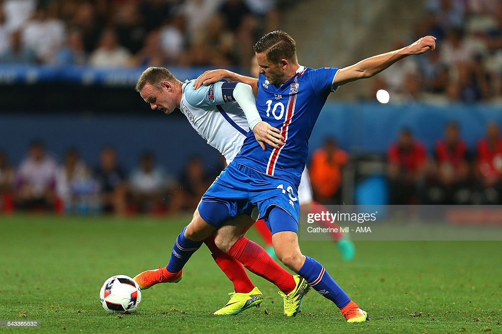 <a gi-track='captionPersonalityLinkClicked' href=/galleries/search?phrase=Gylfi+Sigurdsson&family=editorial&specificpeople=6401581 ng-click='$event.stopPropagation()'>Gylfi Sigurdsson</a> of Iceland tangles with <a gi-track='captionPersonalityLinkClicked' href=/galleries/search?phrase=Wayne+Rooney&family=editorial&specificpeople=157598 ng-click='$event.stopPropagation()'>Wayne Rooney</a> of England during the UEFA Euro 2016 Round of 16 match between England and Iceland at Allianz Riviera Stadium on June 27, 2016 in Nice, France.