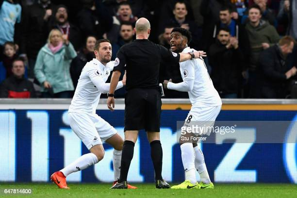 Gylfi Sigurdsson of Swansea City and Leroy Fer of Swansea City appeal to referee Anthony Taylor after he awards Burnley a penalty during the Premier...