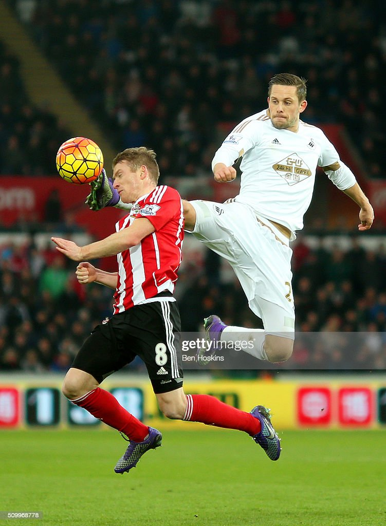 Gylfi Sigurdsson of Swansea City and Steven Davis of Southampton compete for the ball during the Barclays Premier League match between Swansea City and Southampton at Liberty Stadium on February 13, 2016 in Swansea, Wales.