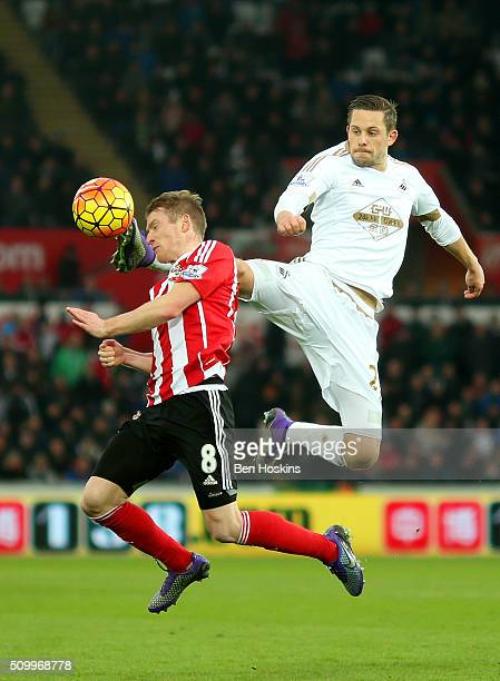 Gylfi Sigurdsson of Swansea City and Steven Davis of Southampton compete for the ball during the Barclays Premier League match between Swansea City...