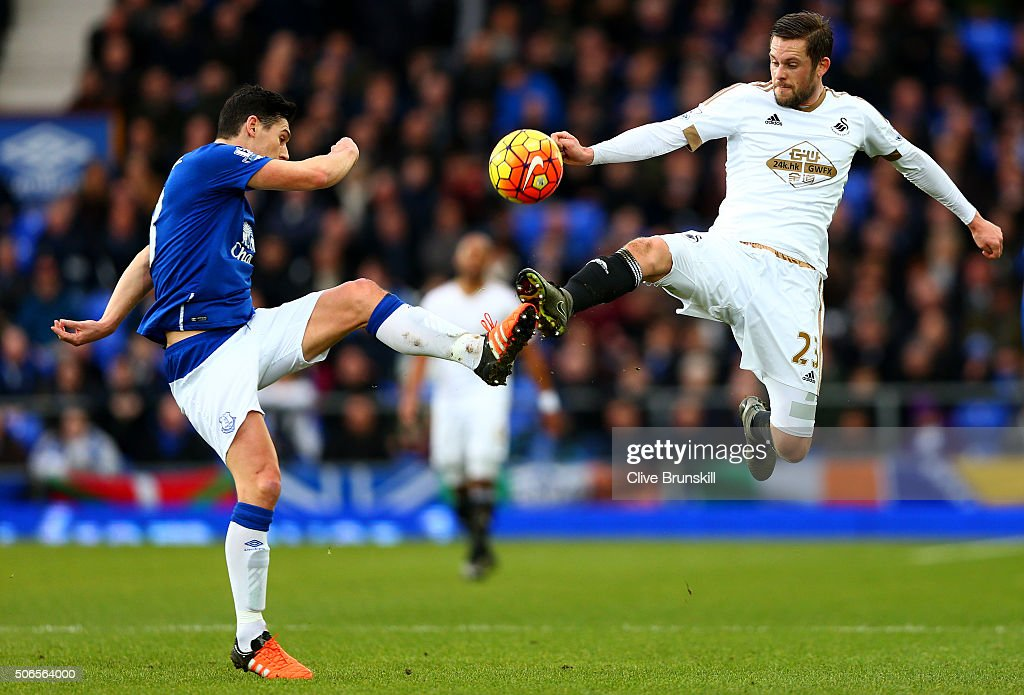Gylfi Sigurdsson of Swansea City battles for the ball with Gareth Barry of Everton during the Barclays Premier League match between Everton and Swansea City at Goodison Park on January 24, 2016 in Liverpool, England.