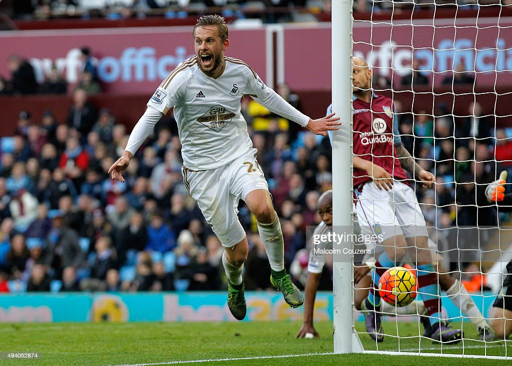 Gylfi Sigurdsson of Swansea City celebrates his team's second goal by Andre Ayew (obscured) during the Barclays Premier League match between Aston Villa and Swansea City at Villa Park on October 24, 2015 in Birmingham, England.