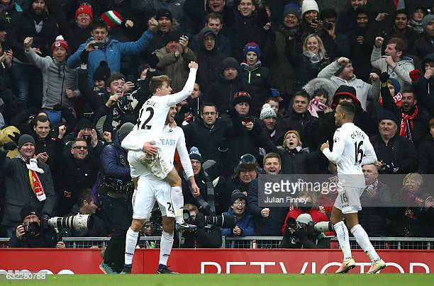 Gylfi Sigurdsson of Swansea City celebrates scoring his sides third goal with Tom Carroll of Swansea City and Wayne Routledge of Swansea City during...