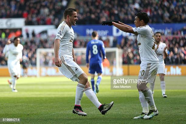Gylfi Sigurdsson of Swansea City celebrates scoring his team's first goal with his team mate Jefferson Montero during the Barclays Premier League...