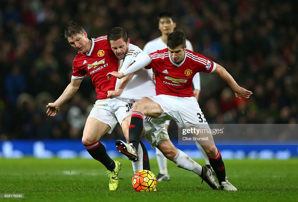 Gylfi Sigurdsson (C) of Swansea City competes for the ball against Bastian Schweinsteiger (L) and Paddy McNair (R) of Manchester United during the Barclays Premier League match between Manchester United and Swansea City at Old Trafford on January 2, 2016 in Manchester, England.