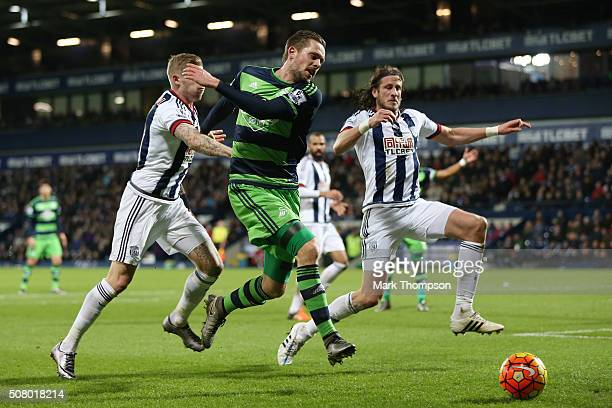 Gylfi Sigurdsson of Swansea City competes for the ball against James McClean and Jonas Olsson of West Bromwich Albion during the Barclays Premier...