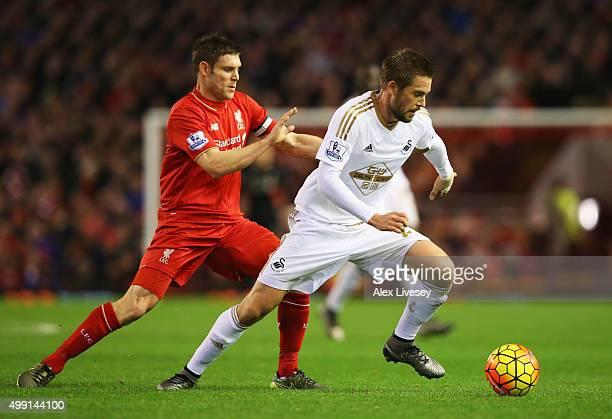 Gylfi Sigurdsson of Swansea City evades James Milner of Liverpool during the Barclays Premier League match between Liverpool and Swansea City at...