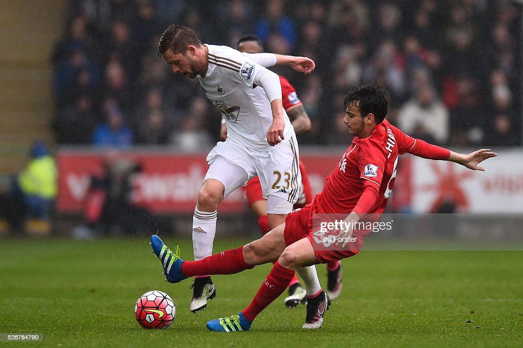 Gylfi Sigurdsson of Swansea City is tackled by Pedro Chirivella of Liverpool during the Barclays Premier League match between Swansea City and Liverpool at The Liberty Stadium on May 1, 2016 in Swansea, Wales.