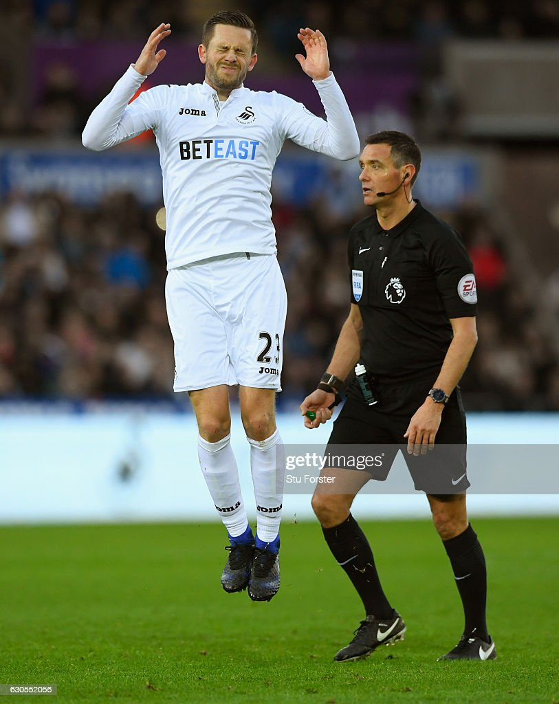 Gylfi Sigurdsson of Swansea City reacts after his free kick is saved as referee Andre Marriner looks on during the Premier League match between Swansea City and West Ham United at Liberty Stadium on December 26, 2016 in Swansea, Wales.
