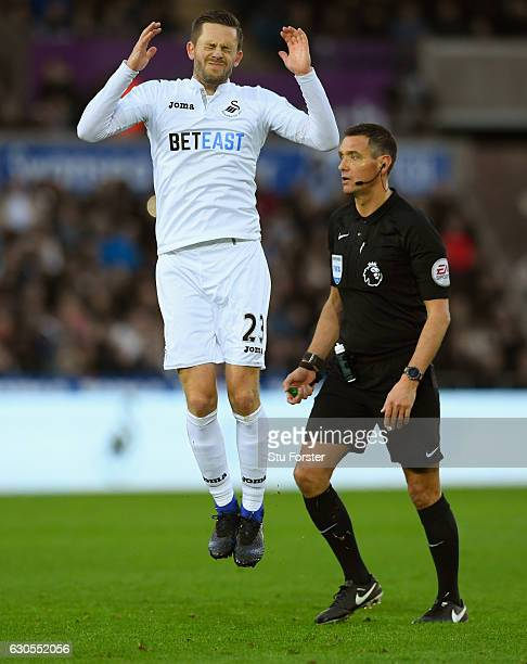 Gylfi Sigurdsson of Swansea City reacts after his free kick is saved as referee Andre Marriner looks on during the Premier League match between...