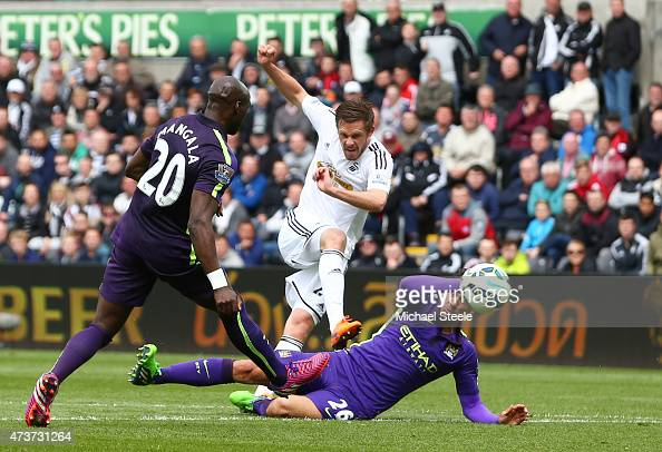 Gylfi Sigurdsson of Swansea City scores a goal despite the challenge from Martin Demichelis of Manchester City during the Barclays Premier League...