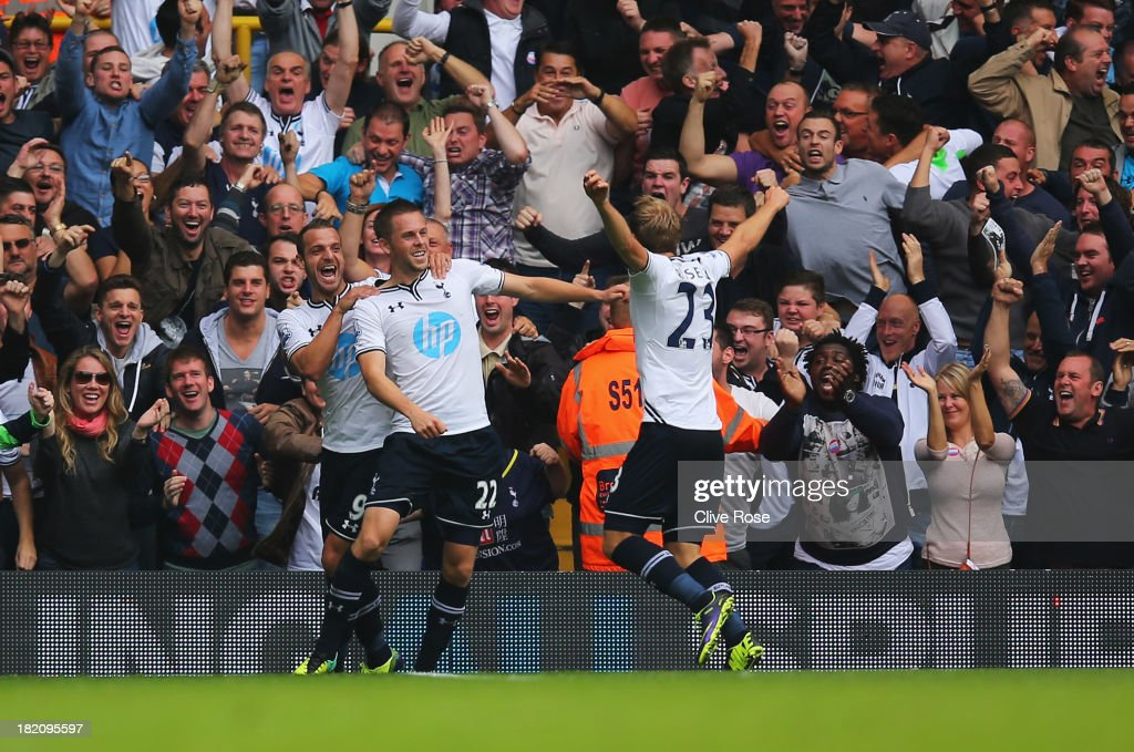 Gylfi Sigurdsson of Tottenham Hotspur (22) celebrates in front of fans with Roberto Soldado (L) and Christian Eriksen (R) during the Barclays Premier League match between Tottenham Hotspur and Chelsea at White Hart Lane on September 28, 2013 in London, England.