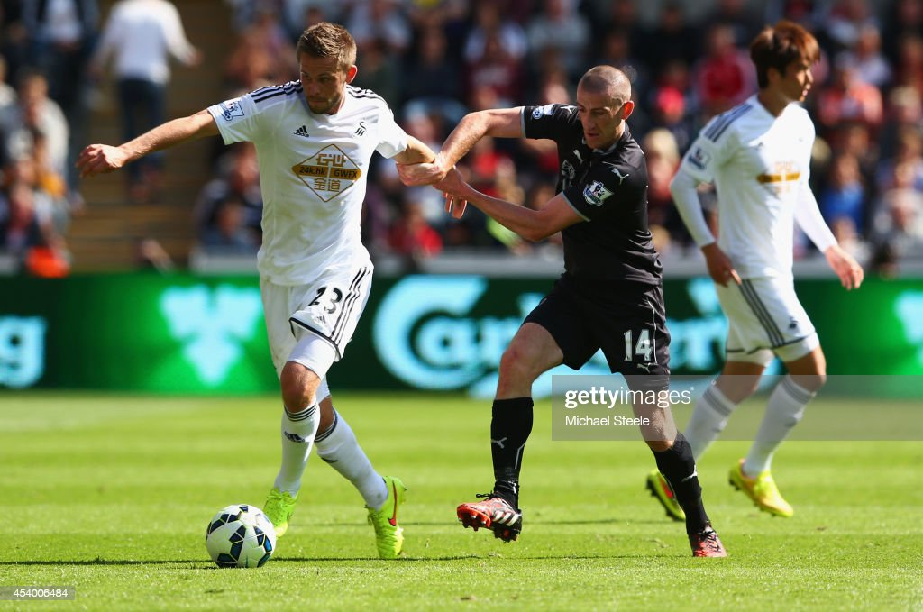 Gylfi Sigurosson of Swansea City holds off David Jones of Burnley during the Barclays Premier League match between Swansea City and Burnley at Liberty Stadium on August 23, 2014 in Swansea, Wales.