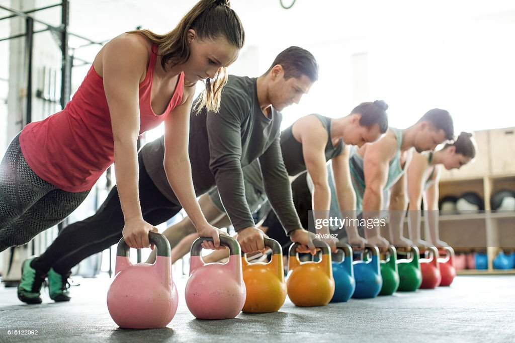 Gym class doing push-ups on kettlebells : Stock-Foto