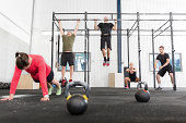 A group training push ups, hang ups and squat at a gym center.