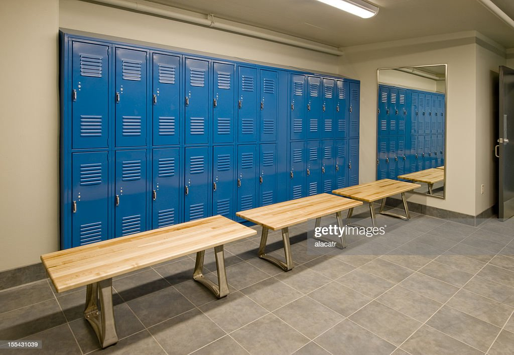 Gym locker room with wooden benches and blue lockers stock