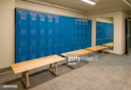 Gym locker room with wooden benches and blue lockers