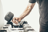 Unrecognizable man taking dumbbells in a gym
