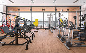 Digitally generated gym scene with wooden floor, a large balcony and a lot of exercise equipment: elliptical trainers, stationary exercising bikes, elliptical trainers, pull-down machines, lever gym m