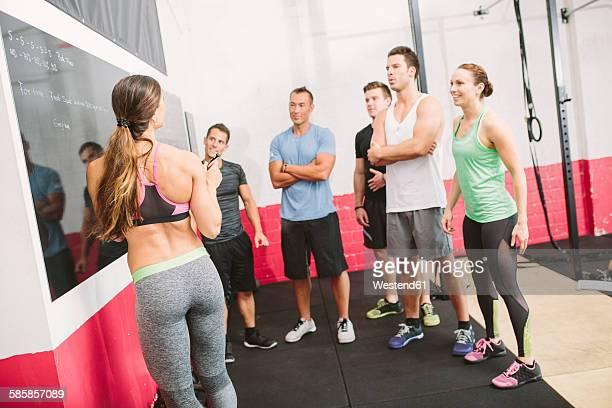 gym trainer explaining exercises at blackboard