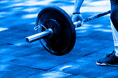 gym woman preparing for her weightlifting workout with a heavy dumbbell. Blue color