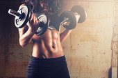 Fitness woman practicing with dumbbells