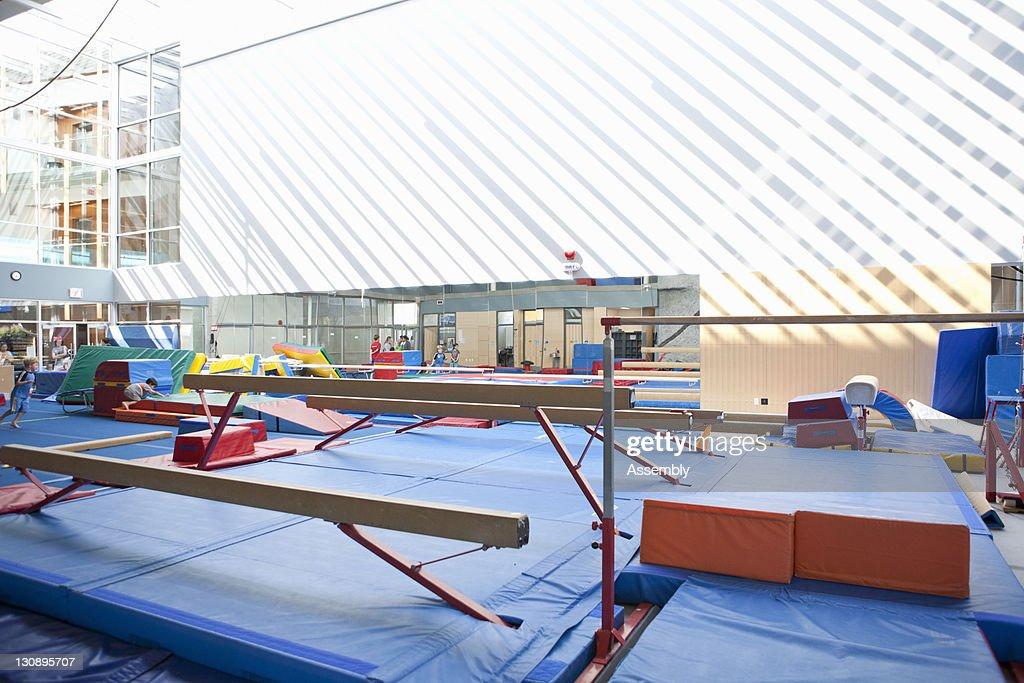Gymnasium interior with balance beams and mats : Stock Photo