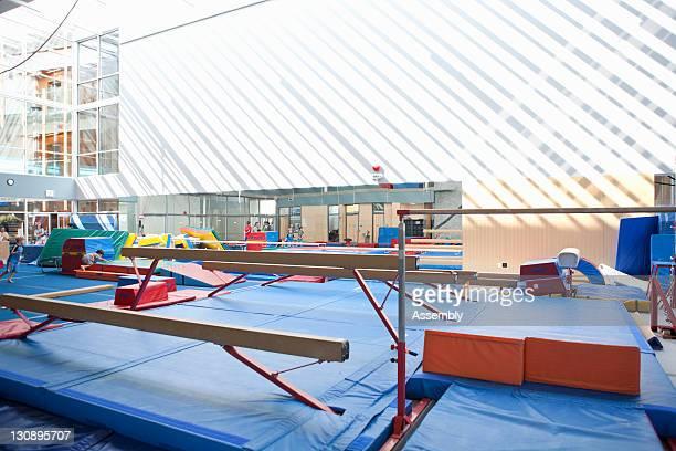 Gymnasium interior with balance beams and mats