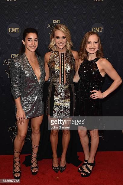 Gymnast Aly Raisman Carrie Underwood and Madison Kocian arrive on the red carpet at CMT Artists of the Year 2016 on October 19 2016 in Nashville...
