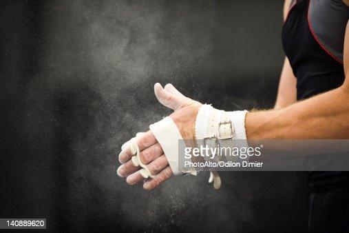 Gymnast applying chalk power to hands in preparation