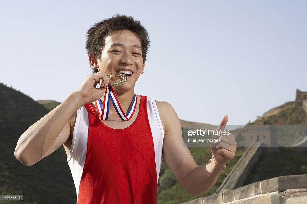 A gymnast biting his metal. : Stock Photo