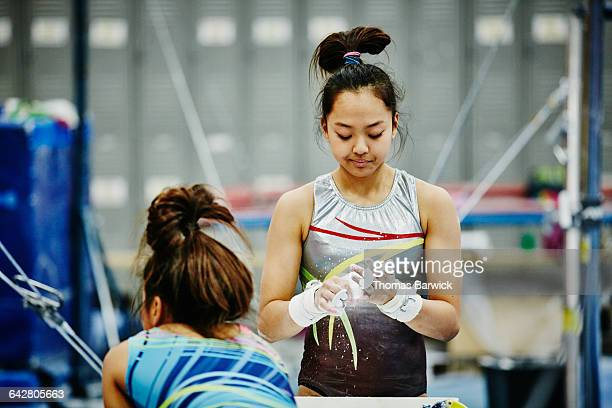 Gymnast chalking hands before practicing on bars
