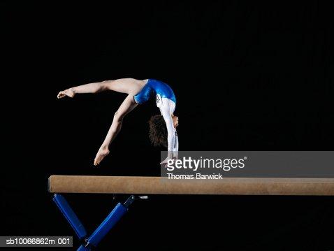 Gymnast (9-10) flipping on balance beam, side view