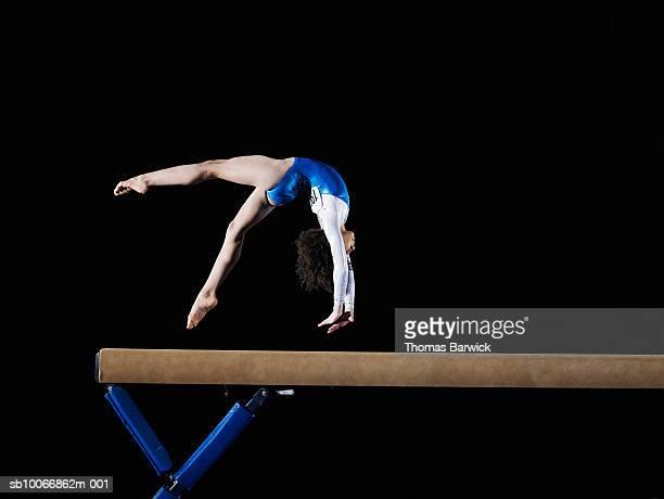 Gymnast (9-10) flipping on balance beam, side view