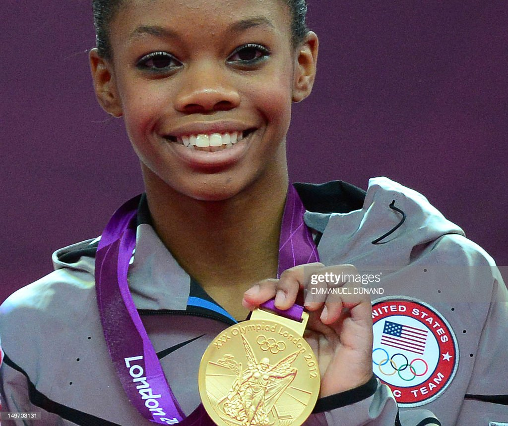 US gymnast Gabrielle Douglas poses on the podium with her gold medal after winning the artistic gymnastics women's individual allaround final at the...