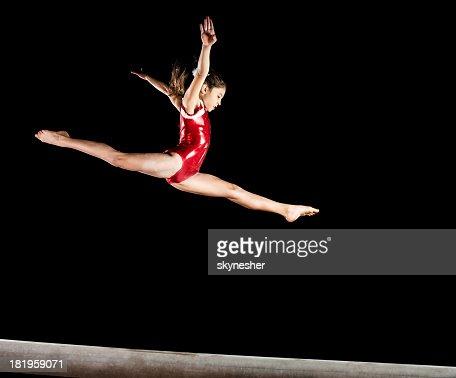 Gymnast girl isolated on black.