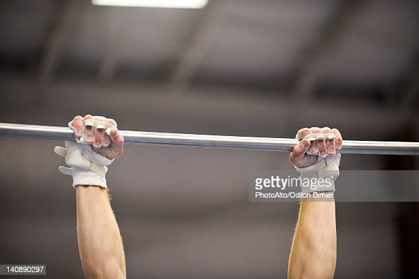 Gymnast gripping horizontal bar, cropped