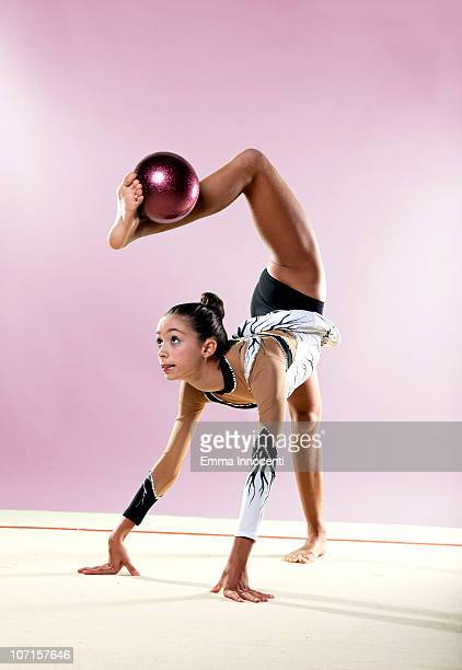 gymnast, holding ball banding backward