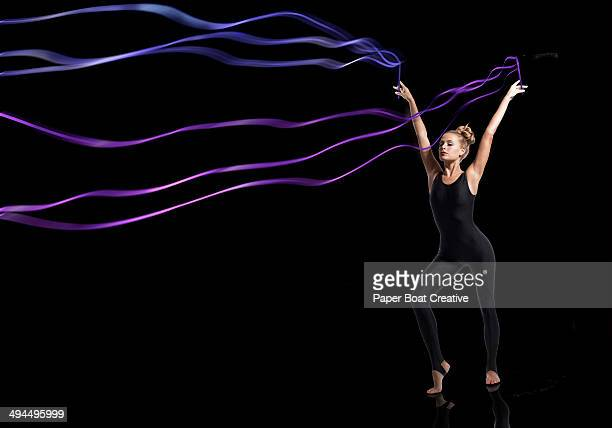 Gymnast holding sets of blue and purple ribbons