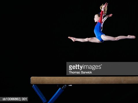 Gymnast (9-10) leaping on balance beam