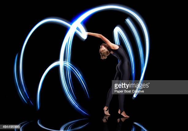 Gymnast making electric blue light streaks