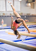 Female gymnast performing a flip on a balance beam. She is catpured in mid-air. High shutter and shallow DOF needed to freeze the action. Image made possible only with modern, top of the line DSLR.