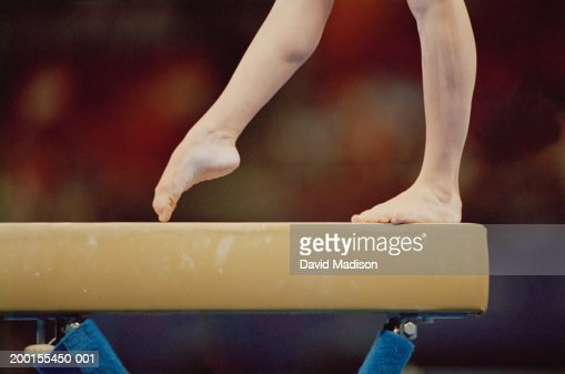 Gymnast on balance beam, low section, close-up