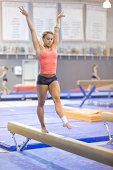 Athletic gymnast concentrates during her balance beam routine. Some grain. Challenging indoor shot made possible only with top of the line modern DSLR camera.
