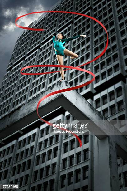 Gymnast on top of structure with ribbon