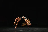 female acrobatic gymnast performing handspring on stage
