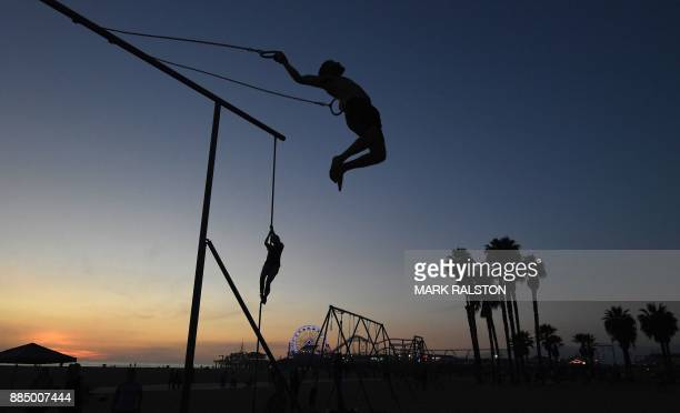 TOPSHOT A gymnast performs on the rings as the sun sets at the original Muscle Beach in Santa Monica California on December 3 2017 The original...